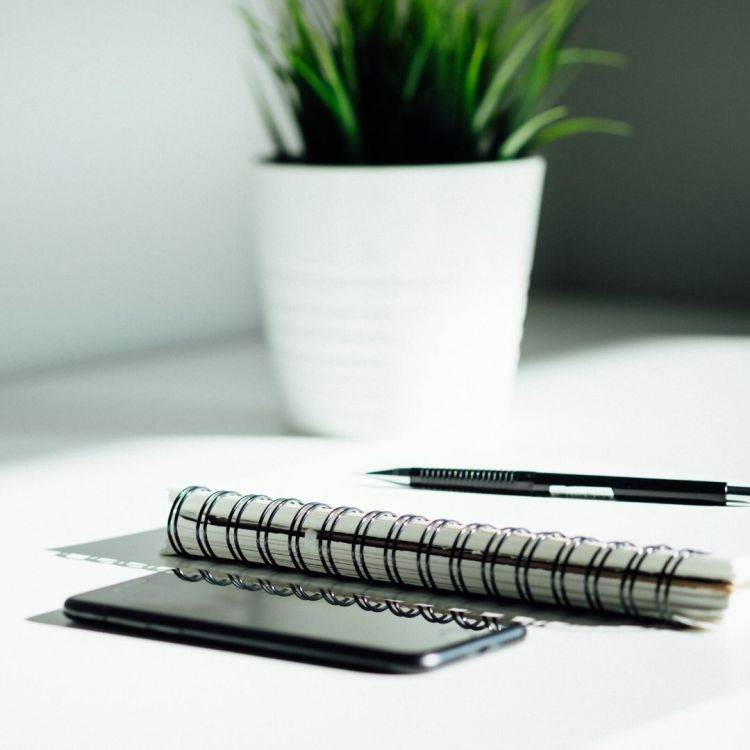 A pad of paper, pen, and iPhone site on a tabletop with a green plant in the aground, to indicate materials associated with a small business marketing blog
